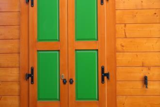 Casa in legno prefabbricata Illegio. Dettaglio porta finestra in legno verniciato
